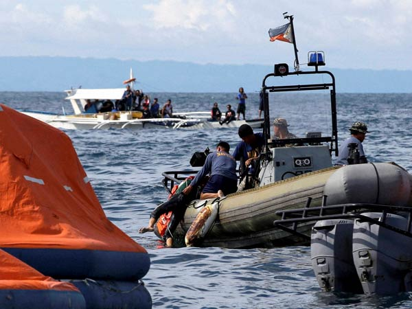 Philippine Navy divers retrieve a body from the waters off the coast of Talisay city, Cebu province, in central Philippines