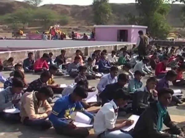 Students write exam on terrace as the dancers perform in school ground