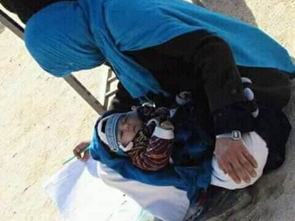 afghan woman writes exam while nursing her baby