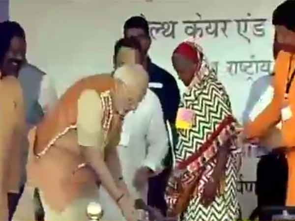 PM Narendra Modi present a pair of slippers to a bare footed lady