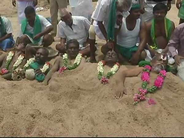 Farmers protesting in Trichy by buried themselves in Cauvery river sand