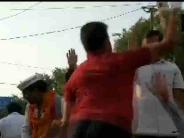 A man slaps Delhi Chief Minister Arvind Kejriwal during his roadshow
